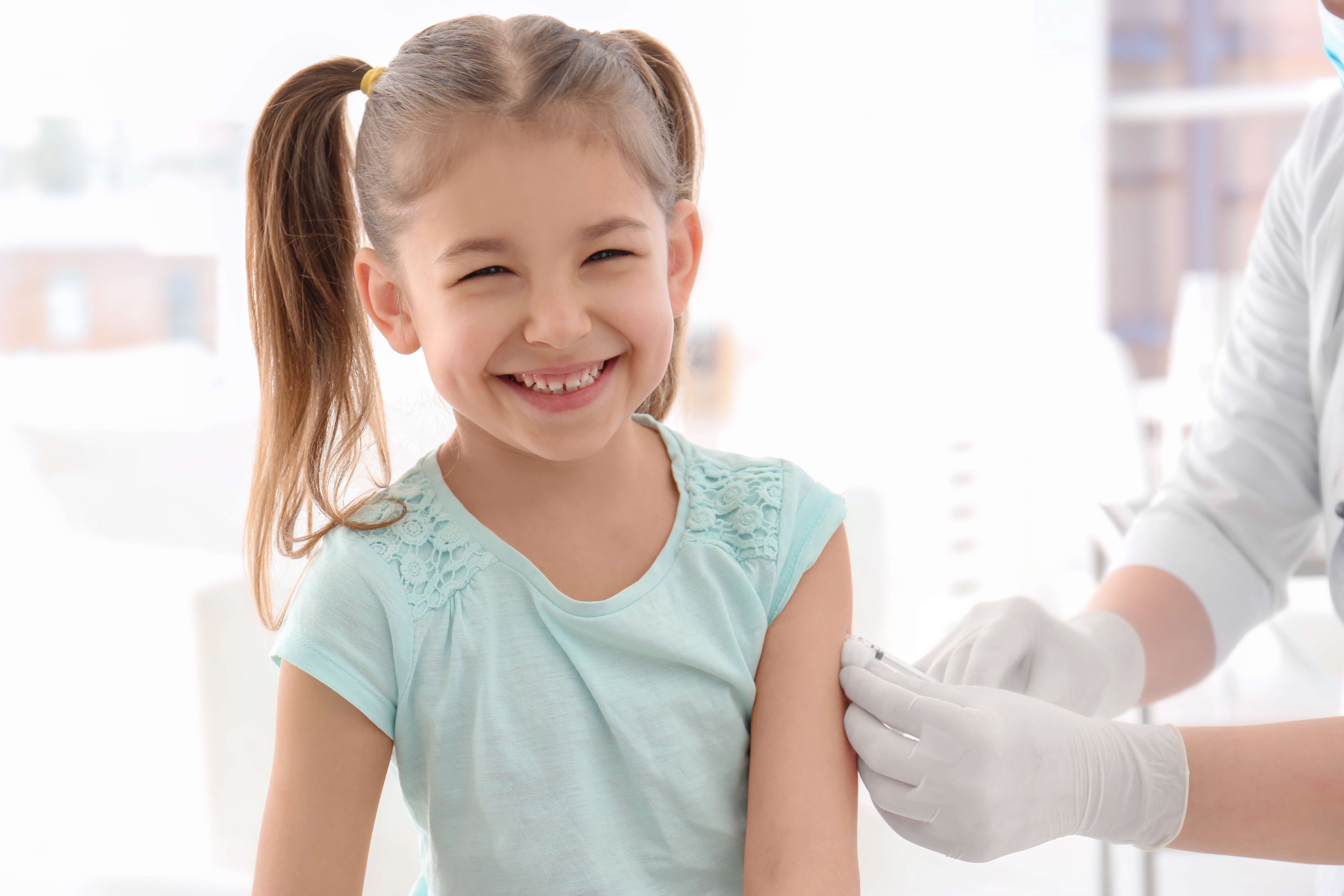 Doctor vaccinating little girl in hospital